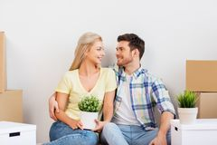 Happy couple with boxes moving to new home royalty free stock photography