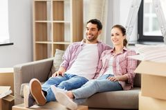 Happy couple with boxes moving to new home stock photos