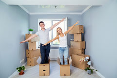 Happy couple with boxes in the room of the new apartment. stock images