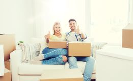 Happy couple with boxes showing thumbs up at home Stock Image