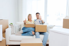 Happy couple with boxes showing thumbs up at home Stock Photography