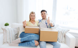 Happy couple with boxes showing thumbs up at home Royalty Free Stock Images
