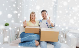 Happy couple with boxes showing thumbs up at home Royalty Free Stock Photo