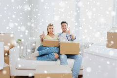 Happy couple with boxes showing thumbs up at home Royalty Free Stock Image