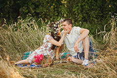 Happy couple of boyfriend and girlfriend sitting among grass in meadow at picnic. Woman embracing and touching her husband by hand Stock Photos