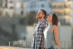Happy couple breathing fresh air in a town. E view portrait of a happy couple breathing fresh air in a town street royalty free stock images