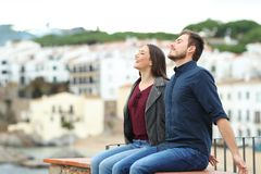 Happy couple breathing on a ledge on vacation royalty free stock image