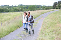 Happy couple of breeders walking in countryside Stock Images
