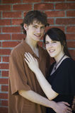 Happy couple by brick wall. A happy young couple in front of brick wall stock photos