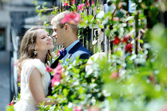 Happy couple bride and groom near flowers and plants in wedding day. Happy romantic couple bride and groom near flowers and plants in wedding day Stock Photos