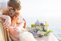Happy couple bride and groom sitting in a chair on the shore of a lake Royalty Free Stock Photos