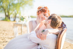 Happy couple bride and groom sitting in a chair on the shore of a lake Royalty Free Stock Images