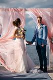 Happy couple, the bride and groom, stand on the pier under the wedding arch. Sunny day Royalty Free Stock Image