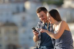 Happy couple browsing cell phone content in a town. Happy couple browsing cell phone online content in a town outskirts royalty free stock images