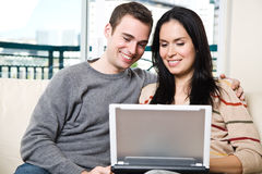 Happy couple browsing internet at home Stock Photography