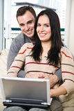 Happy couple browsing internet at home Royalty Free Stock Image