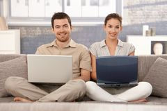 Happy couple browsing internet at home smiling. Happy couple sitting on sofa at home, browsing internet on separate laptops, smiling, having fun Stock Photos