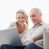 Happy couple browsing internet on laptop Stock Photo
