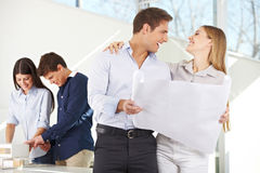Happy couple with building plan. For their new house in architecture office Royalty Free Stock Photography