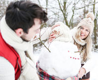 Happy couple building snowman Royalty Free Stock Photography