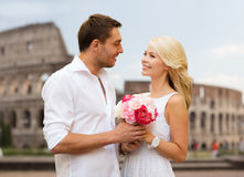 Happy couple with bunch of flowers over coliseum Royalty Free Stock Images