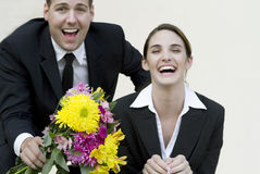 Happy couple in business suits with bouquet royalty free stock images
