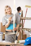 Happy couple busy renovating painting new home. Happy casual, caucasian couple busy renovating painting new home. Baseball cap, bucket, ladder Stock Photography