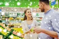 Happy couple buying apples at grocery store Stock Photo