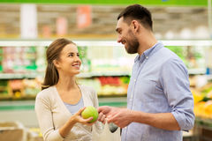 Happy couple buying apples at grocery store Stock Image