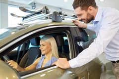 Happy couple buying car in auto show or salon Stock Photography