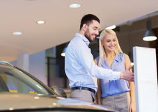 Happy couple buying car in auto show or salon Stock Photo