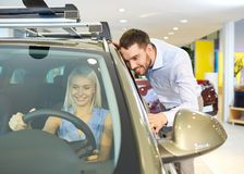 Happy couple buying car in auto show or salon Royalty Free Stock Photo