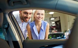 Happy couple buying car in auto show or salon Royalty Free Stock Photography