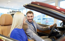 Happy couple buying car in auto show or salon Stock Image