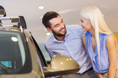 Happy couple buying car in auto show or salon Stock Photos