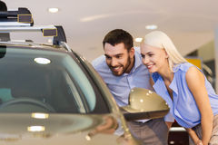 Happy couple buying car in auto show or salon Royalty Free Stock Photos