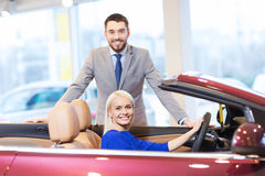 Happy couple buying car in auto show or salon Royalty Free Stock Images