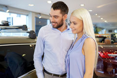 Happy couple buying car in auto show or salon Stock Images