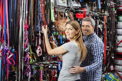Happy Couple Buying Leash At Pet Store Royalty Free Stock Photography