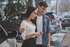 Happy couple buying new car at dealership salon royalty free stock photos