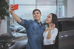 Happy couple buying new car at dealership salon royalty free stock photography
