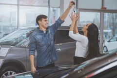 Happy couple buying new car at dealership salon stock photos