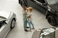 Happy couple buying new car together at the dealership royalty free stock photography