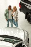 Happy couple buying new car together at the dealership royalty free stock image