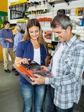 Happy Couple Buying Tool Set In Hardware Store. With people hand shaking in background Stock Photography