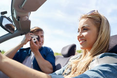 Happy couple with camera driving in cabriolet car Royalty Free Stock Image