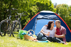 Happy couple on a camping drinking prosecco Stock Image