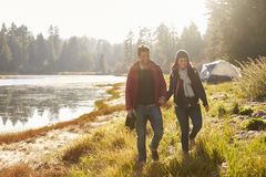 Happy couple on camping trip walk near a lake holding hands Stock Image