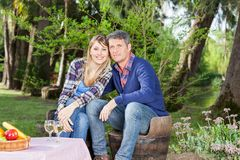 Happy Couple At Campsite. Portrait of happy couple sitting on chairs at campsite royalty free stock photos
