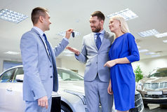 Happy couple with car dealer in auto show or salon Royalty Free Stock Photos